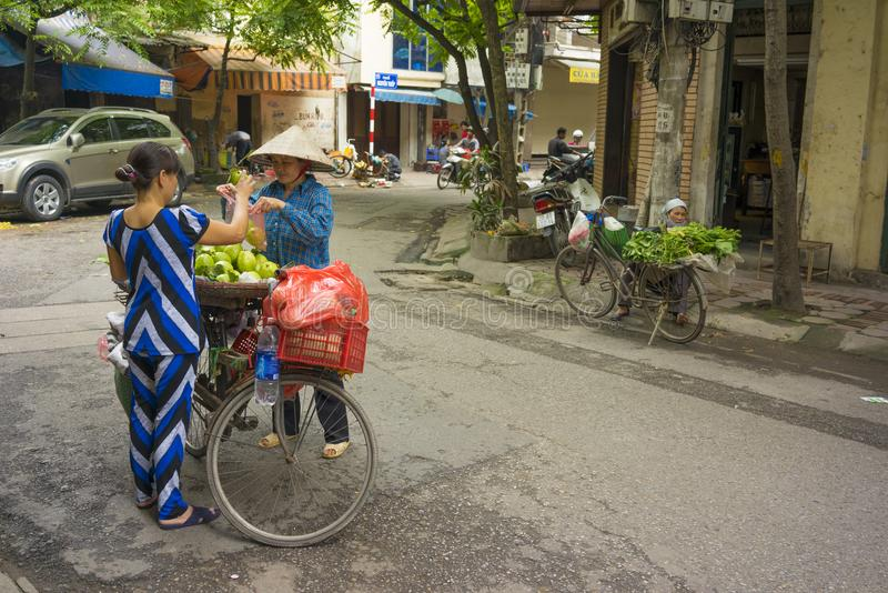 Hanoi, Vietnam - April 13, 2014: Unidentified food vendor sells fruits carried by bike to a woman on Hanoi street, Vietnam royalty free stock photos