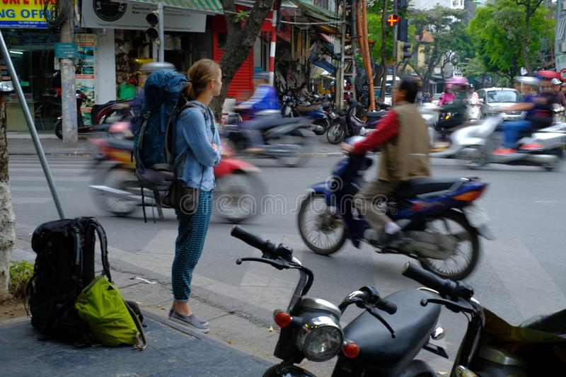 Hanoi / Vietnam, 05/11/2017: Backpacker watching busy hectic traffic with passing cars and motorbikes on a Hanoi street stock image