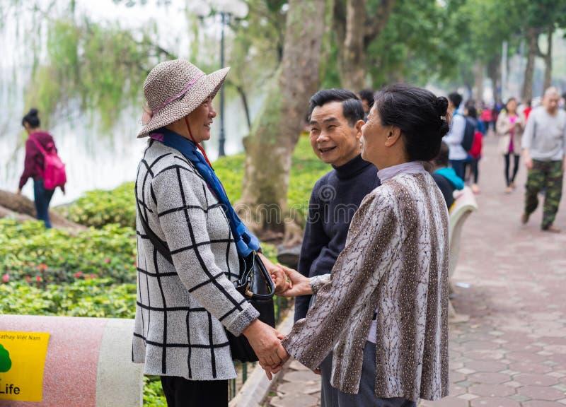 Hanoi, Vietnam - breng 15, 2015 in de war: Een paar die gelukkig hun vriend zien bij het meer van Hoan Kiem, het district van Hoa stock afbeeldingen