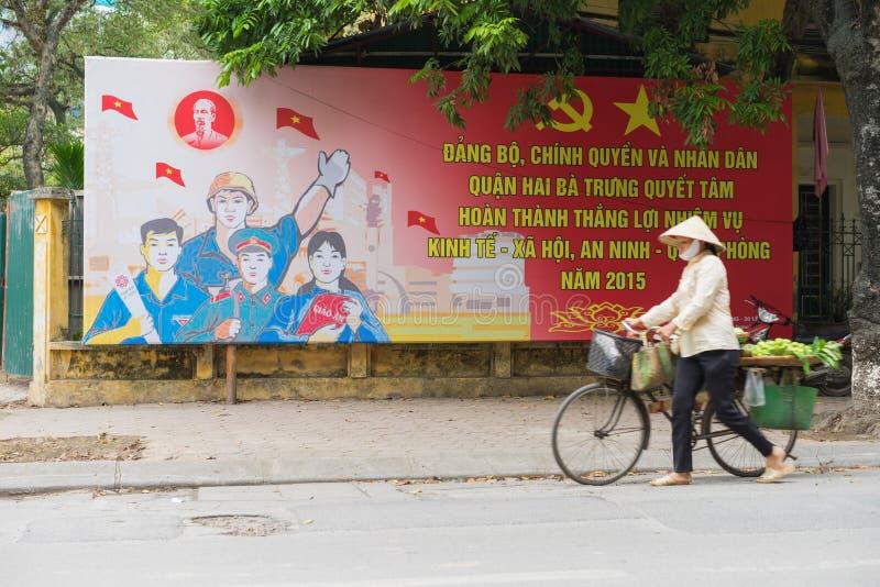 Hanoi, Vietnam - breng 29, 2015 in de war: Een verkoper die gaat binnen een communistische propaganda tot de straat van Hien over royalty-vrije stock fotografie