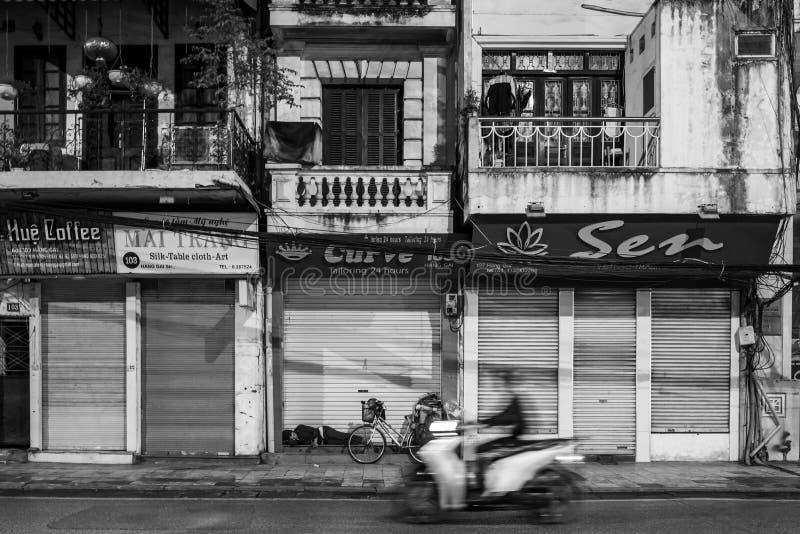 Hanoi, Vietnam - 14 de abril de 2018: La vespa conduce delante de hombre durmiente en las calles de Hanoi fotos de archivo libres de regalías