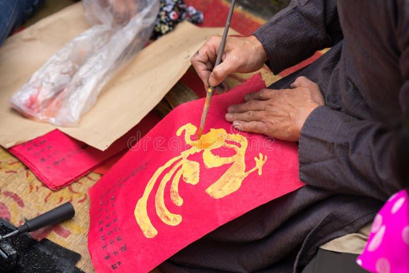 Hanoi, Vietnam - 22 de junio de 2017: Viejo artista del pueblo de Dong Ho que hace Dong Ho la pintura popular del grabar en mader foto de archivo libre de regalías