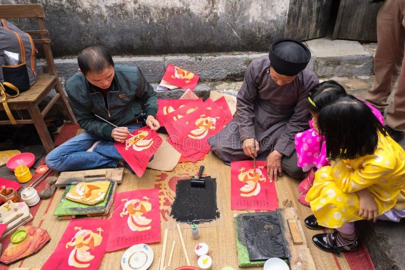 Hanoi, Vietnam - 22 de junio de 2017: Viejo artista del pueblo de Dong Ho que hace Dong Ho la pintura popular del grabar en mader fotos de archivo libres de regalías