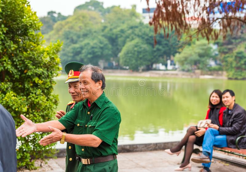 HANOI, VIETNAM - DECEMBER 16, 2016: De bejaarden in eenvormig in de stad parkeren Exemplaarruimte voor tekst stock afbeeldingen