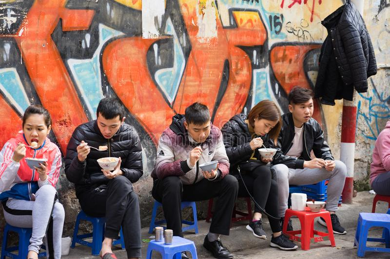 Hanoi, Vietnam - Feb 28, 2016: Customers have their meal on the street stall. Vietnamese people love to eat delicious food on side stock photo