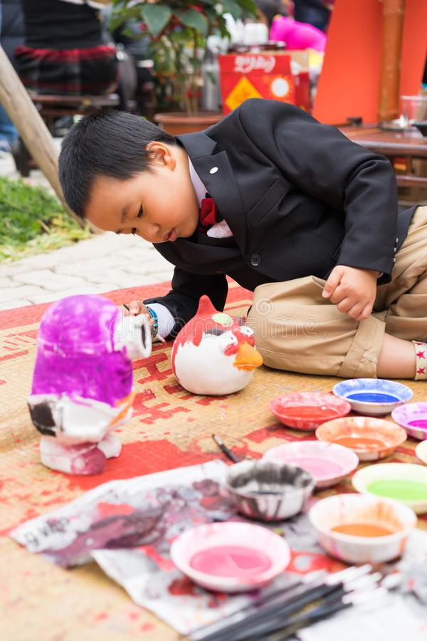 Hanoi, Vietnam - Feb 7, 2015: Schoolboy learn to paint plaster figurine by brush and color ink at Vietnamese lunar new year festiv stock image