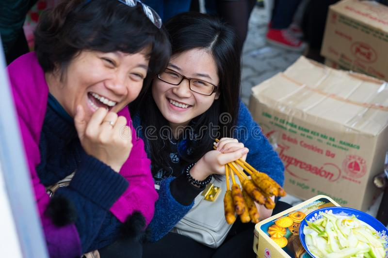 Hanoi, Vietnam - Feb 7, 2015: Two smiling girls sell fastfood at Vietnamese lunar new year festival organized at Vinschool, Vinhom royalty free stock images