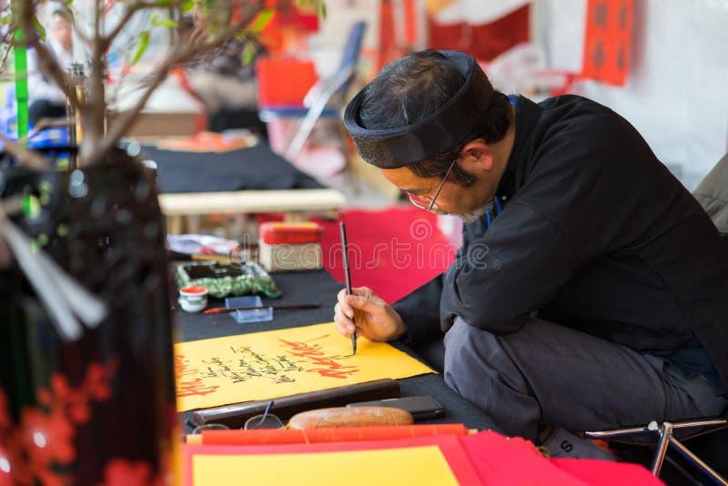 Hanoi, Vietnam - Feb 15, 2015: Vietnamese scholar at lunar new year calligraphy festival organizing at Temple of Literature Van Mi. Eu royalty free stock image