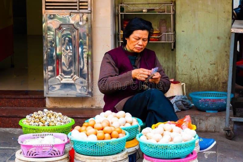 HANOI VIETNAM - Februari 13, 2018: En kvinna som säljer ägg på en gammal gatamarknad i Hanoi, Vietnam royaltyfria bilder