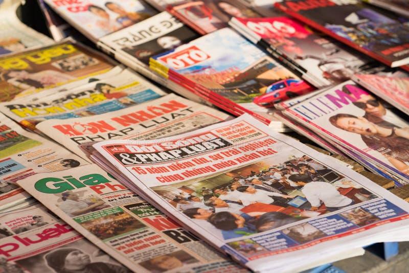Hanoi, Vietnam - 28 Februari, 2016: Vietnamese kranten voor verkoop op nieuwstribune in de straat van Hanoi stock foto's