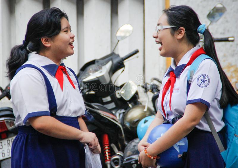 Two students of a high school girl with red Soviet ties are talking at a break and laughing merrily. Hanoi, Vietnam - February 23, 2016: two students of a high royalty free stock image
