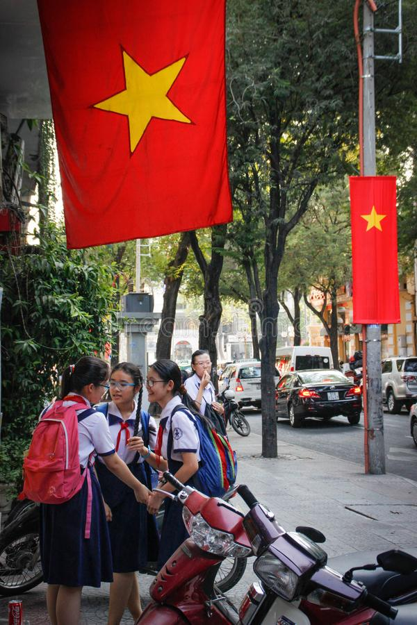Two students of a high school girl with red Soviet ties are talking at a break and laughing merrily under the red Vietnamese state royalty free stock photos