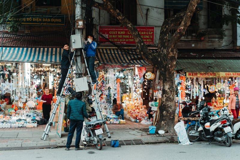 Hanoi, Vietnam, 12 20 18: Het leven in de straat in Hanoi De elektricien probeert om één of ander probleem met de elektriciteit t stock fotografie