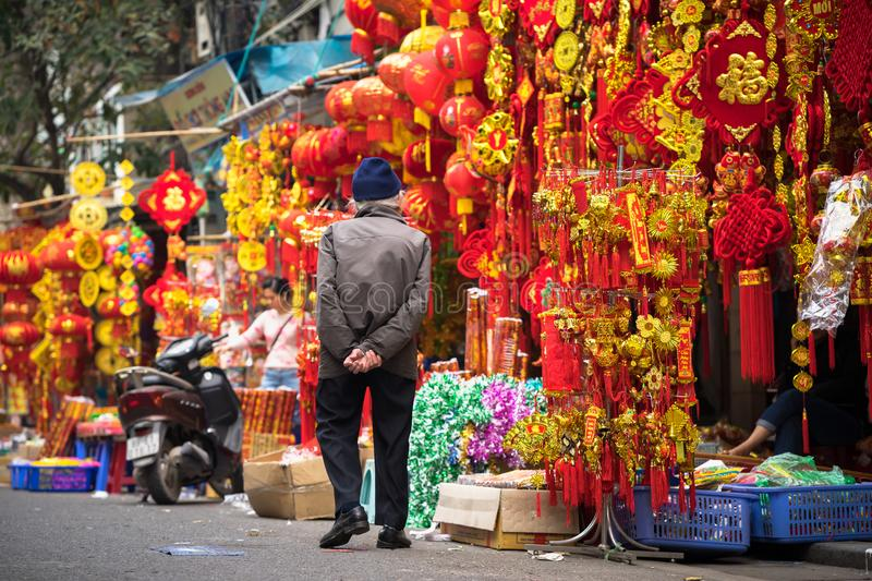 Hanoi, Vietnam - Jan 26, 2017: Old man take a walk buying decoration and flower for Vietnamese lunar new year on Hang Ma street.  stock images