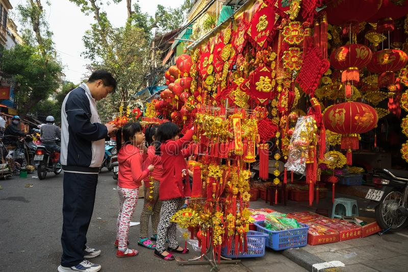 Hanoi, Vietnam - Jan 26, 2017: People take a walk buying decoration and flower for Vietnamese lunar new year on Hang Ma street.  royalty free stock image