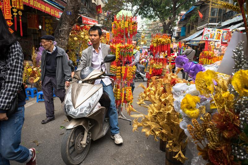Hanoi, Vietnam - Jan 26, 2017: People take a walk buying decoration and flower for Vietnamese lunar new year on Hang Ma street.  stock photos