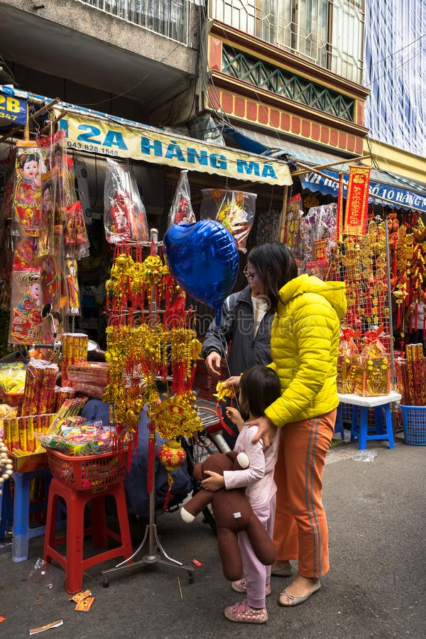 Hanoi, Vietnam - Jan 26, 2017: People take a walk buying decoration and flower for Vietnamese lunar new year on Hang Ma street.  royalty free stock photo