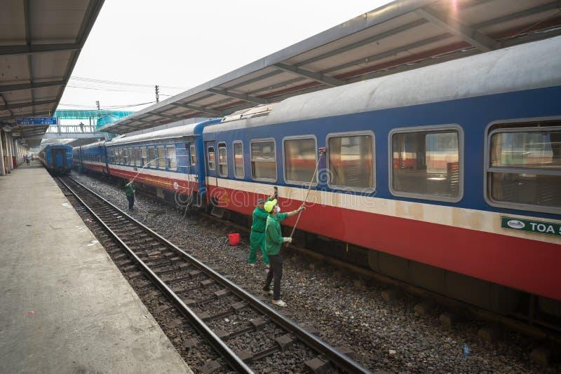 Hanoi, Vietnam - 26 Januari, 2017: Arbeiders die trein schoonmaken bij het station van Hanoi, de straat van Le Duan stock foto