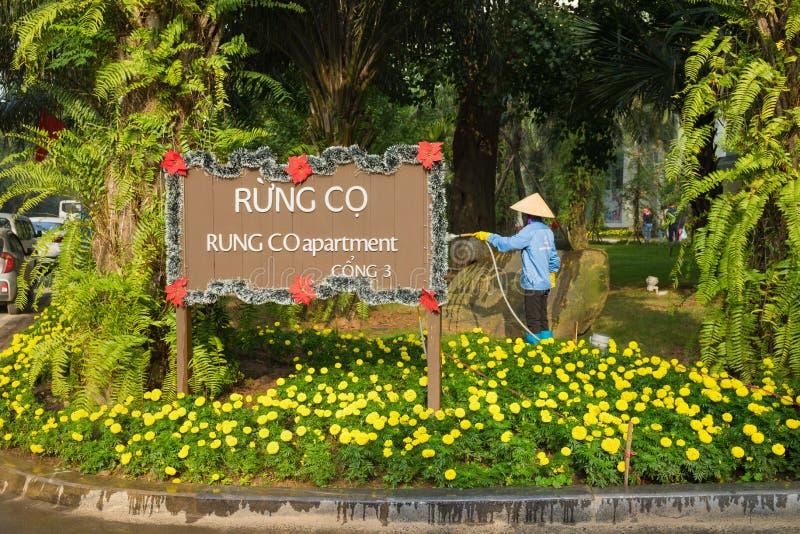 Hanoi, Vietnam - 1 Januari, 2016: Het teken van de Aparmentraad met Aziatische vrouw die een groene en bloementuin water geven bi royalty-vrije stock foto