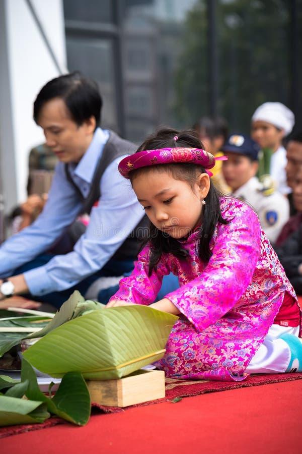 Hanoi Vietnam - Januari 14, 2017: Traditionell klänning Ao Dai som för liten flickakläder lär att göra Chung att baka ihop vid hä arkivfoto