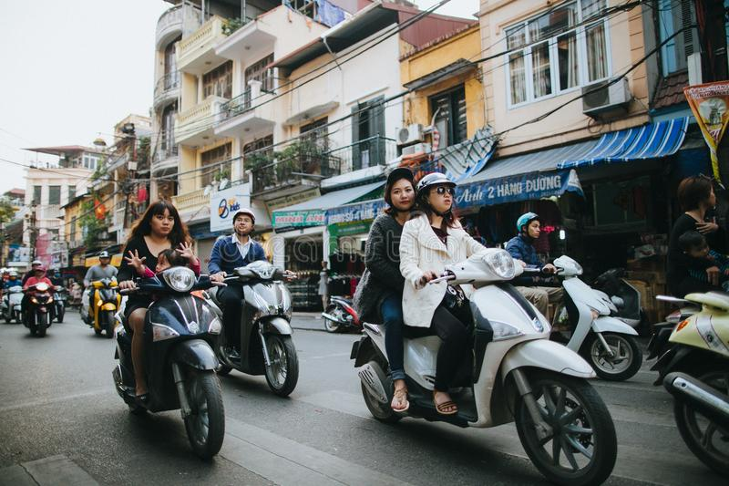People riding motorbikes on busy street in Hanoi, Vietnam. HANOI, VIETNAM - 03 JANUARY, 2018: people riding motorbikes on busy street in Hanoi, Vietnam royalty free stock image