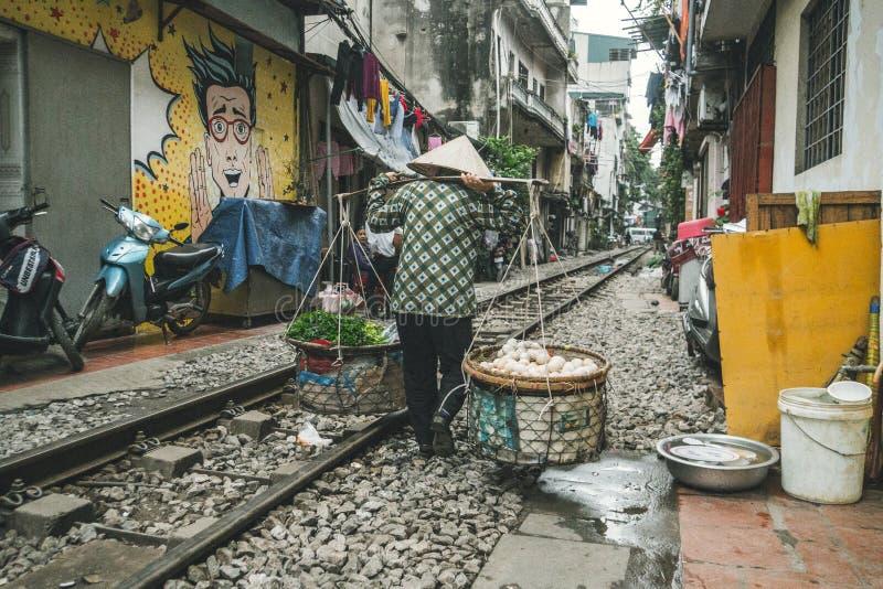 Hanoi. Vietnam. 13 January 2019: woman carries a traditional yoke with food by railway running along narrow street stock photos