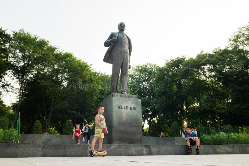 Hanoi Vietnam - Juli 10, 2016: Den Vladimir Ilyich Lenin statyn, med barn som spelar leken i Lenin, parkerar, den Dien Bien Phu g arkivfoto