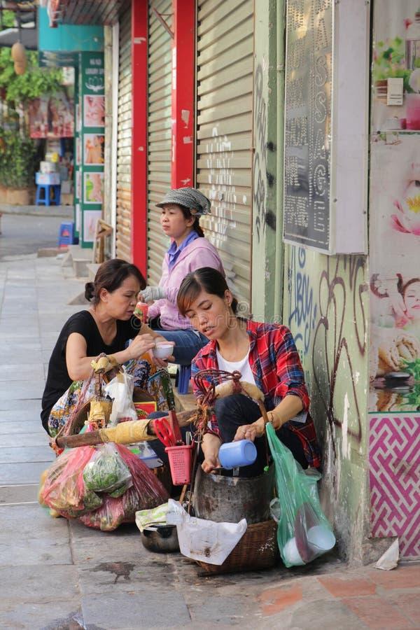 Hanoi, Vietnam - Juli 05,2019: Een vrouwenwinkelbediende verkoopt voedsel in de straat stock foto