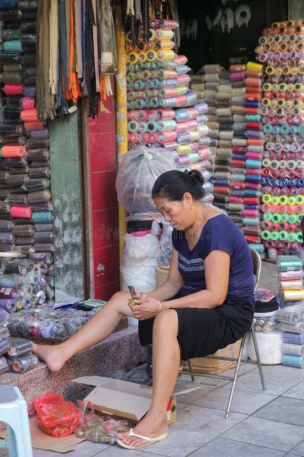 Hanoi Vietnam - Juli 05,2019: En kvinnaaffärsbiträde skalar frukt av hennes shoppar framme, när hon har fri tid royaltyfri fotografi
