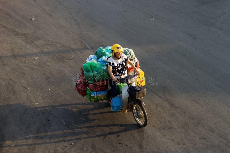 Hanoi Vietnam - Juli 23, 2016: Flyg- sikt av den vietnamesiska kvinnan som transporterar frukt med motorcykeln på den Yen Phu gat royaltyfri bild