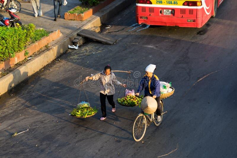 Hanoi Vietnam - Juli 23, 2016: Flyg- sikt av vietnamesiska kvinnaförsäljare som bär frukt på den Yen Phu gatan i otta arkivbilder