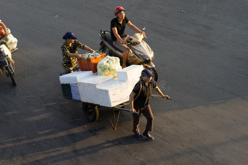 Hanoi, Vietnam - July 23, 2016: Aerial view of Vietnamese women transporting fruit by pull cart on Yen Phu street in early morning.  royalty free stock photos