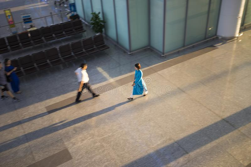 Hanoi, Vietnam - July 12, 2015: Blurred panning effect on Vietnamese air stewardess wearing Ao Dai walks at Hall of Noi Bai Intern royalty free stock photos