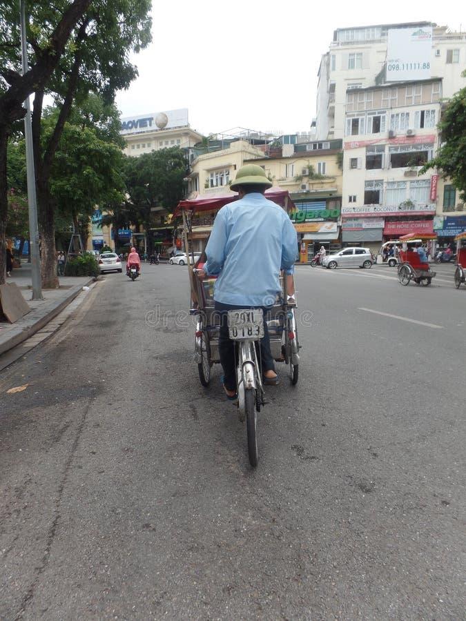 Hanoi, Vietnam - July 27 2019: Rickshaw driver in city centre royalty free stock photography