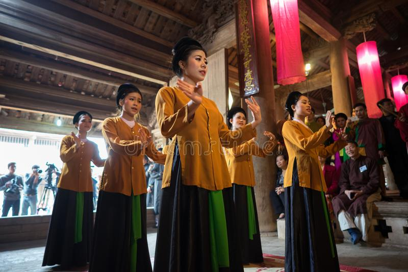 Hanoi, Vietnam - Jun 22, 2017: Dancers dancing with traditional folk music in communal house at So village, Quoc Oai district. stock image