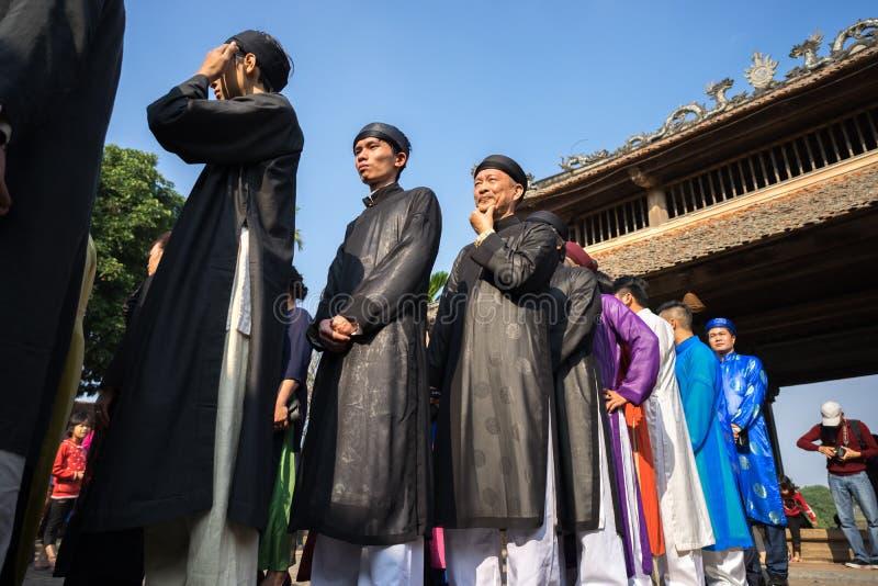 Hanoi, Vietnam - Jun 22, 2017: Vietnamese men wear traditional long dress Ao Dai standing at ancient village in communal house at royalty free stock photos
