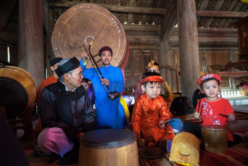 Hanoi Vietnam - Juni 22, 2017: Vietnamesisk gammal traditionell folk sångare med barn som lär att spela folk instrument i kollekt royaltyfri foto