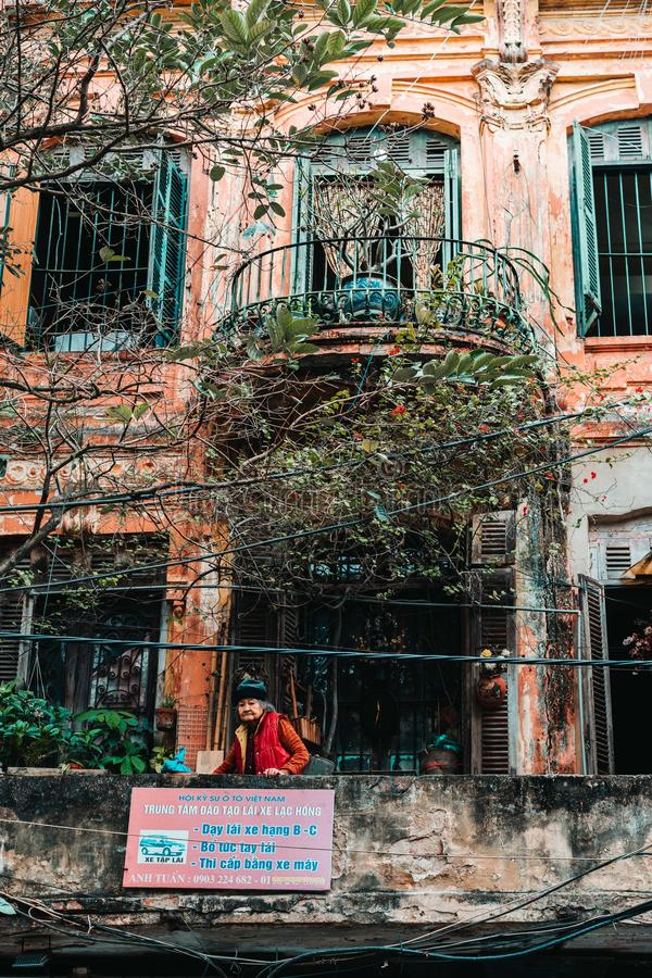 Hanoi, Vietnam, 12.20.18: Life in the street in Hanoi. Old lady on a balcony in an ancient buidling. stock photography
