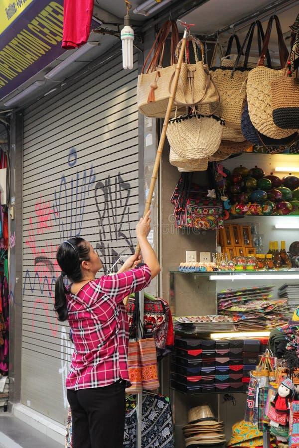 Hanoi, Vietnam - luglio 05,2019: Un commesso della donna sta appendendo le sue borse di mano davanti al negozio alla vendita immagini stock