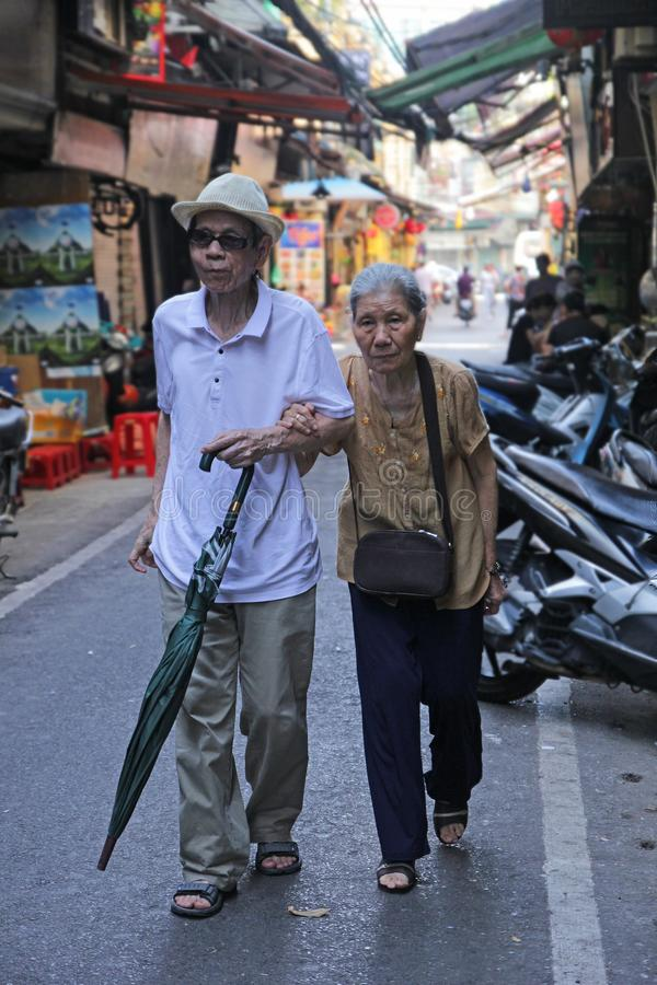 Hanoi, Vietnam - luglio 05,2019: Una vecchia coppia è congiuntamente e camminando insieme nella via fotografia stock libera da diritti