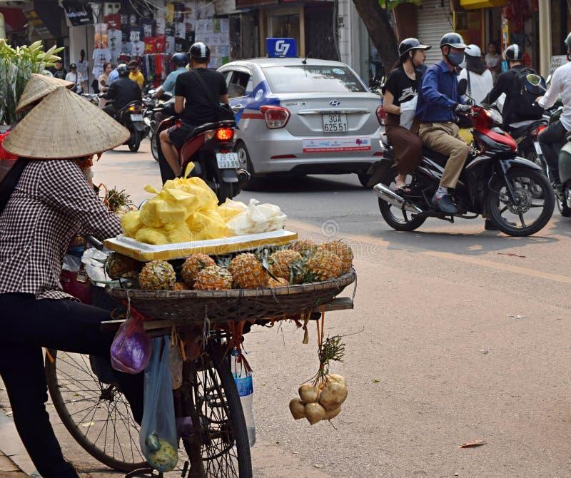 Hanoi, Vietnam, 31 Maart 2019: Een vrouw draagt fruit in manden die aan haar fiets in Vietnam worden vastgebonden stock fotografie