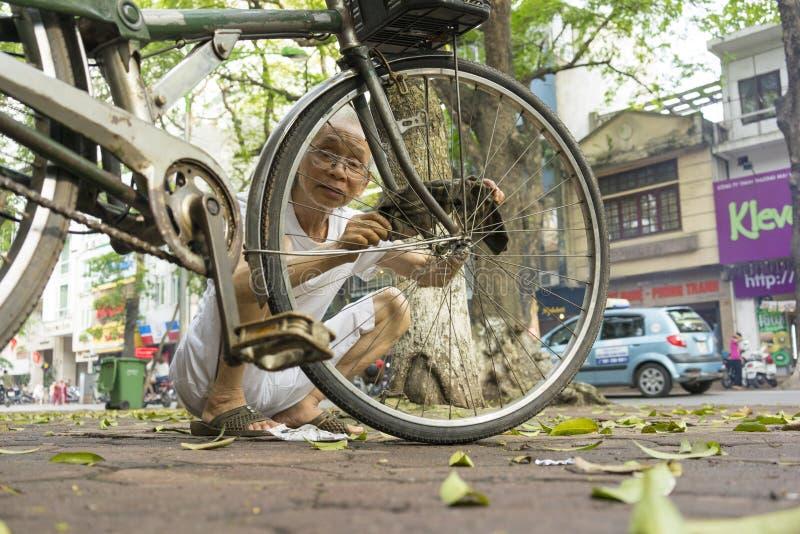 Hanoi Vietnam - Maj 2, 2014: Oidentifierad gamal man som fixar hans cykel på gatasida i den Phan Dinh Phung stren, Hanoi, Vietnam arkivbilder