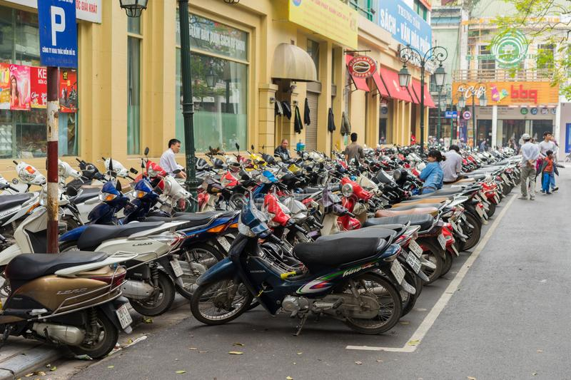 Hanoi, Vietnam - Mar 15, 2015: The parking of motorbikes on street in Trang Tien street. Hanoi lacks of parking area for motorbike. And car royalty free stock images