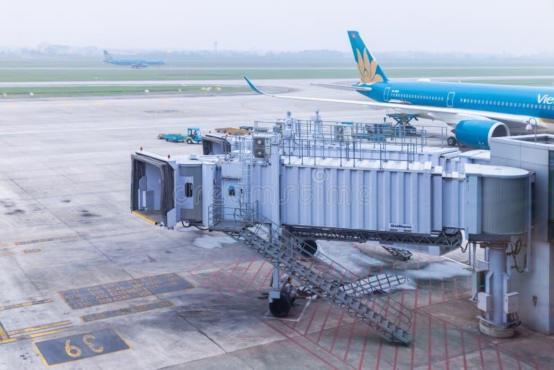 Boarding bridge or jet bridge on prepare by ground service crew for passenger depart or arrive at Noi Bai international airport in. HANOI, VIETNAM - March 9 stock photos