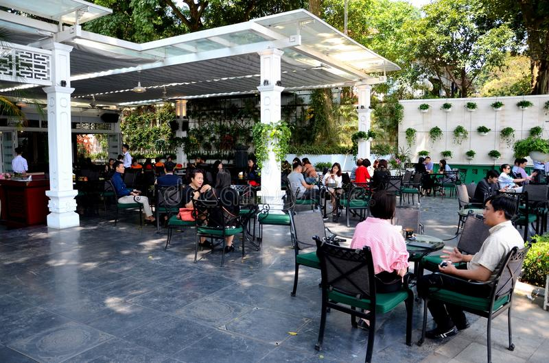 Patrons at outdoor street side upscale cafe in Old Quarter Hanoi Vietnam. Hanoi, Vietnam - March 20, 2018: Groups of casual diners and coffee drinkers sit at a royalty free stock photo