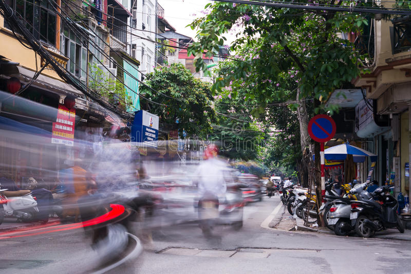 HANOI, VIETNAM - MAY 24, 2017: Hanoi old quarter busy traffic sc. Ene with many motorbikes constantly rushing on the narrow streets long exposure with blurred stock photography