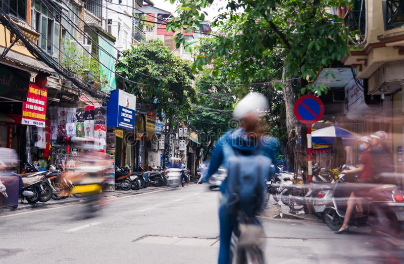 HANOI, VIETNAM - MAY 24, 2017: Hanoi old quarter busy traffic sc. Ene with many motorbikes constantly rushing on the narrow streets long exposure with blurred stock photo