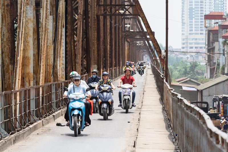 Hanoi, Vietnam - May 2019: people driving scooters and motorbikes on Long Bien bridge stock images