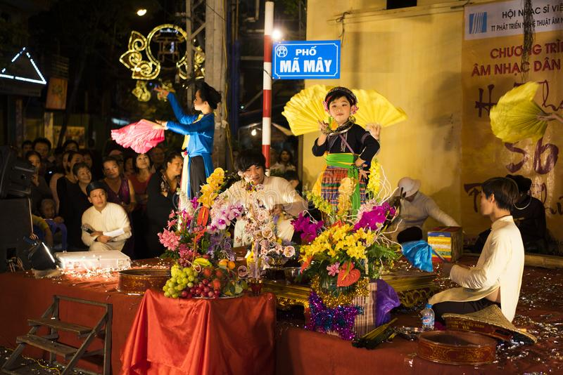 Hanoi, Vietnam - Nov 2, 2014: Vietnamese artists perform folk music and song on Ma May st, old town of Hanoi. The little child pla stock images