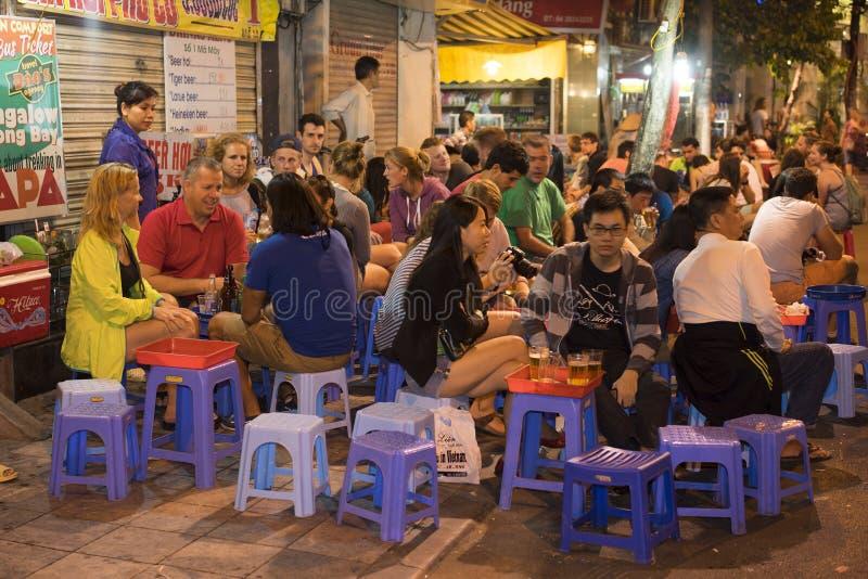Hanoi Vietnam - November 2, 2014: Folket dricker öl på gatan på natten i den gamla fjärdedelen, mitt av Hanoi Att dricka öl på ga royaltyfri foto